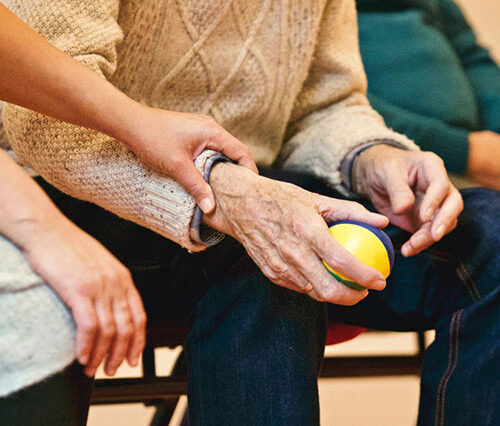 A woman holds an old person's arm close to the hand, as he or she holds a stress ball in that hand. They are both sitting and we can't see their faces. The image represents a cancer coach attending a patient.