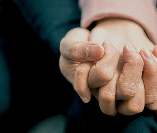 Holding hands with fingers intertwined